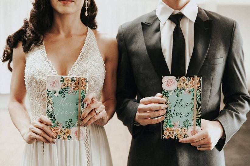 bride and groom holding vow books