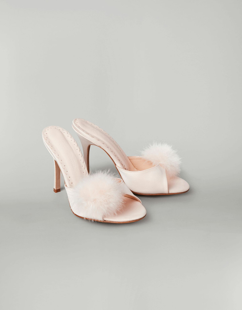 Fluffy blush pink mules on a gray background