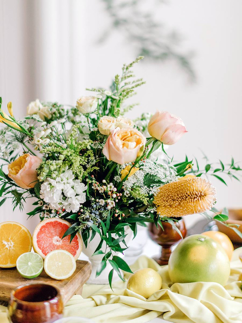 colorful beach wedding centerpiece with peach roses and orange banksia flower with sliced grapefruits, oranges, limes and other fresh citrus on the table