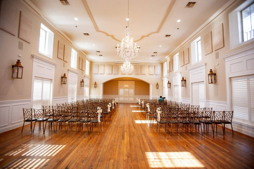 rows of gold chairs arranged in wedding banquet room with hardwood floors and large windows