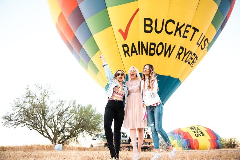 Three women posing in front of rainbow hot air balloon