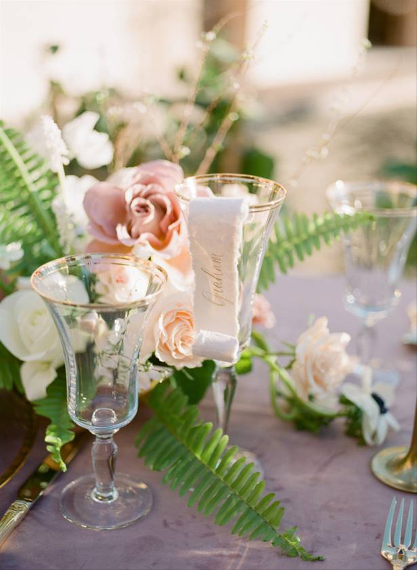 paper scroll place cards are displayed on the rims of crystal wine glasses