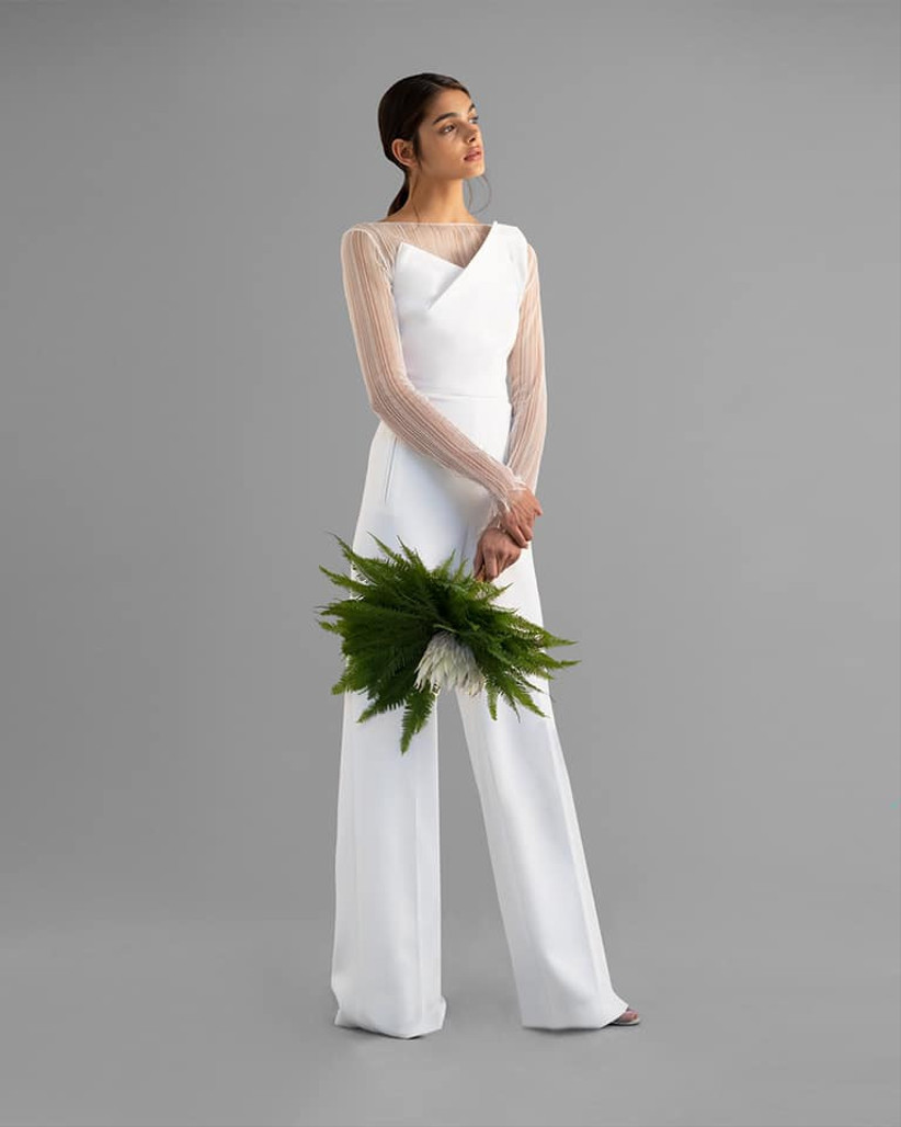 Model wearing chic white jumpsuit with sheer sleeves