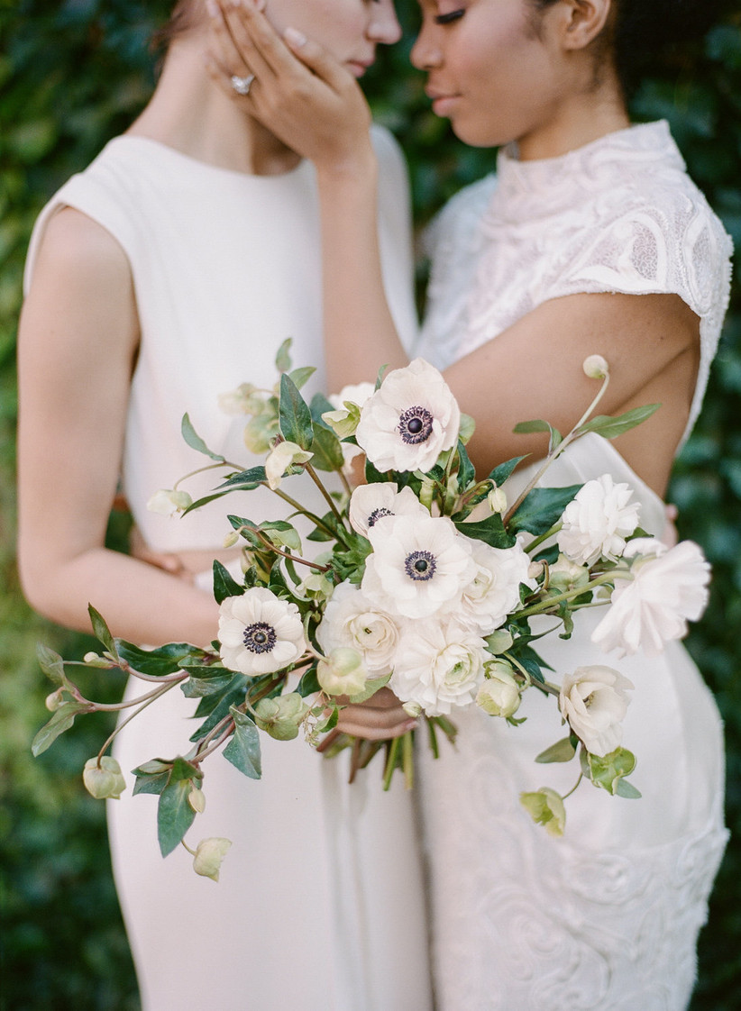 portrait of two brides face to face touching cheeks holding bridal bouquet