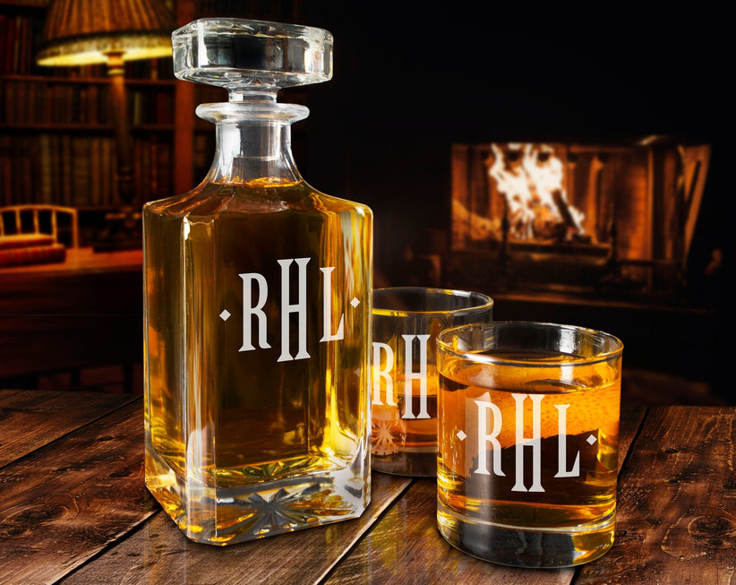 Monogrammed whiskey decanter with two glasses staged in front of a cozy fire
