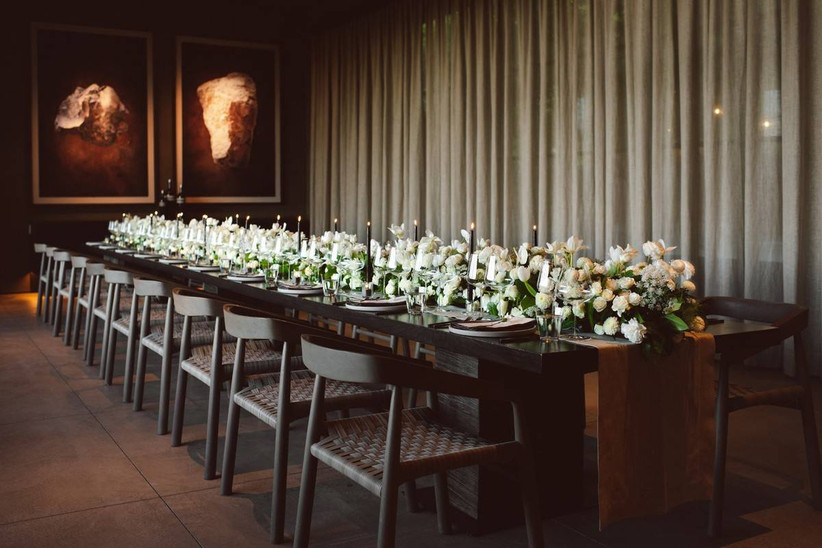 long wedding reception with white floral centerpieces and tall black taper candles down the center
