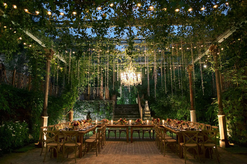 romantic outdoor wedding reception ivy-covered canopy with vines and string lights twinkling