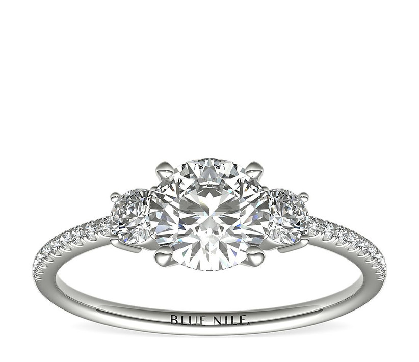 platinum three stone engagement ring with oval diamonds and pave band