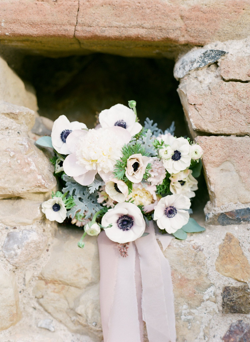 pastel wedding bouquet with anemones, white peonies, greenery, and long blush pink ribbon