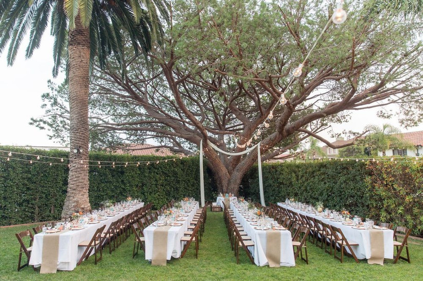 outdoor wedding reception Santa Barbara wedding venue with large historic tree covering secluded garden surrounded by tall hedges