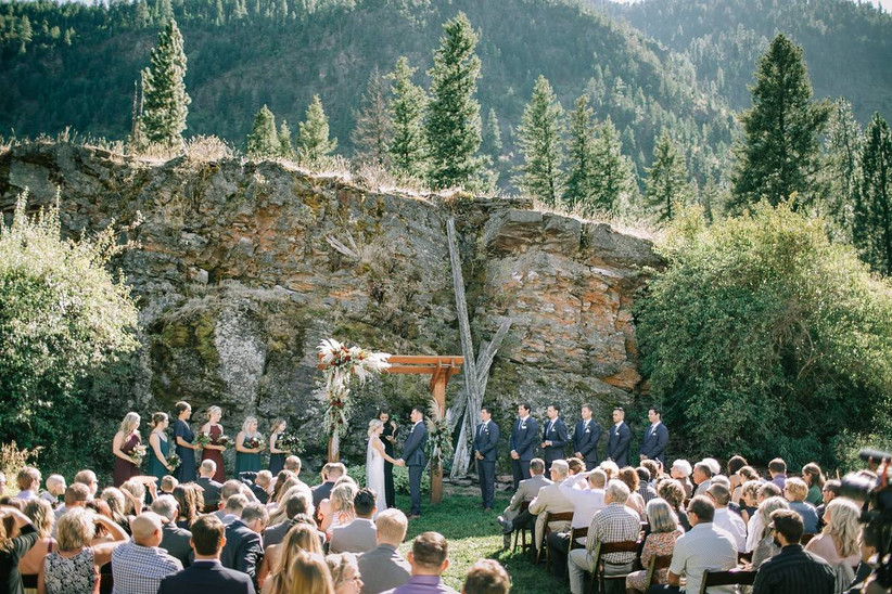 bride and groom stand at the altar outside at mountain wedding venue
