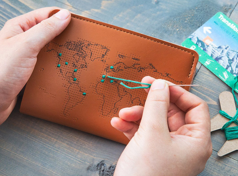 Person stitching a thread into map passport cover to mark travels