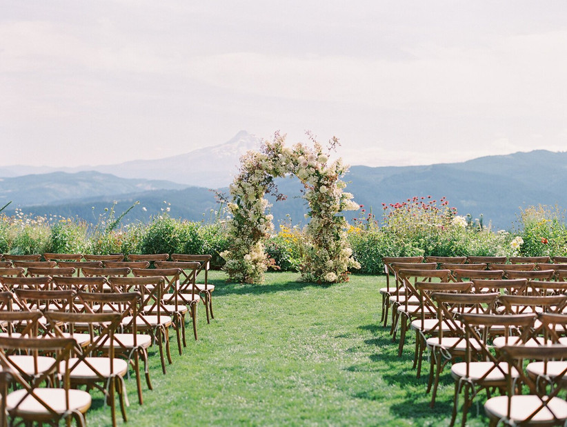 outdoor wedding ceremony with floral arch at altar and mountains in the distance