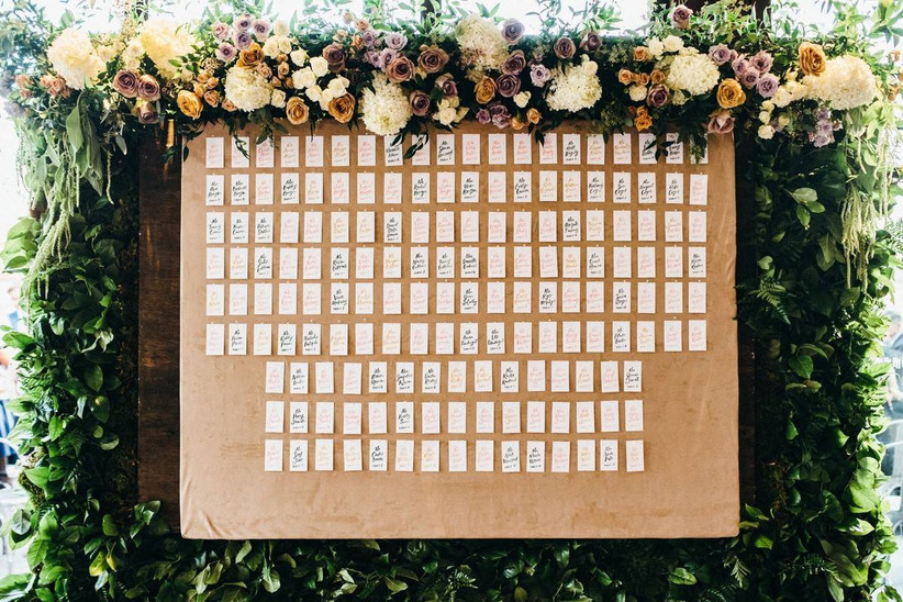 wooden board decorated with handwritten escort cards and fresh flowers