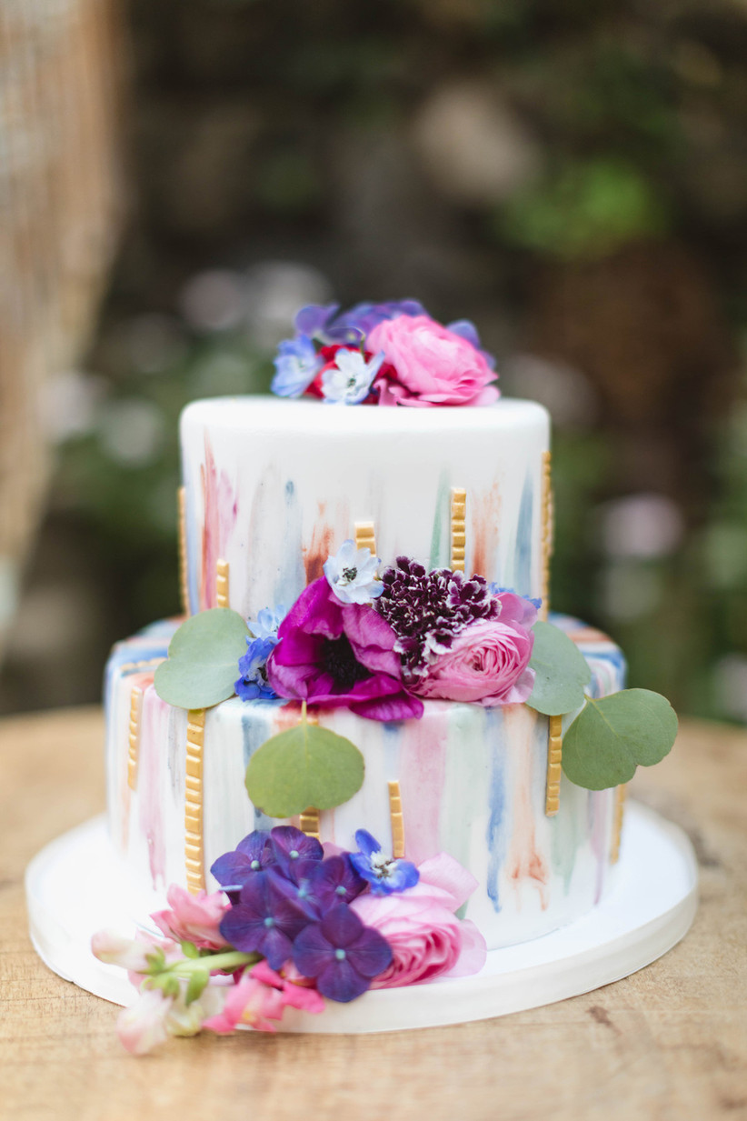 wedding cake decorated with colorful brushstrokes and flowers