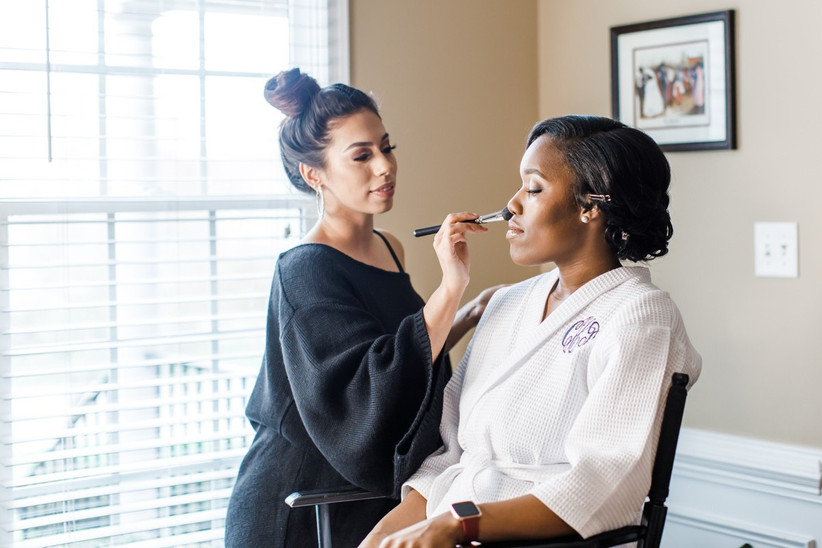 Black bride sits in a chair wearing a white monogrammed robe while her makeup artist applies powder