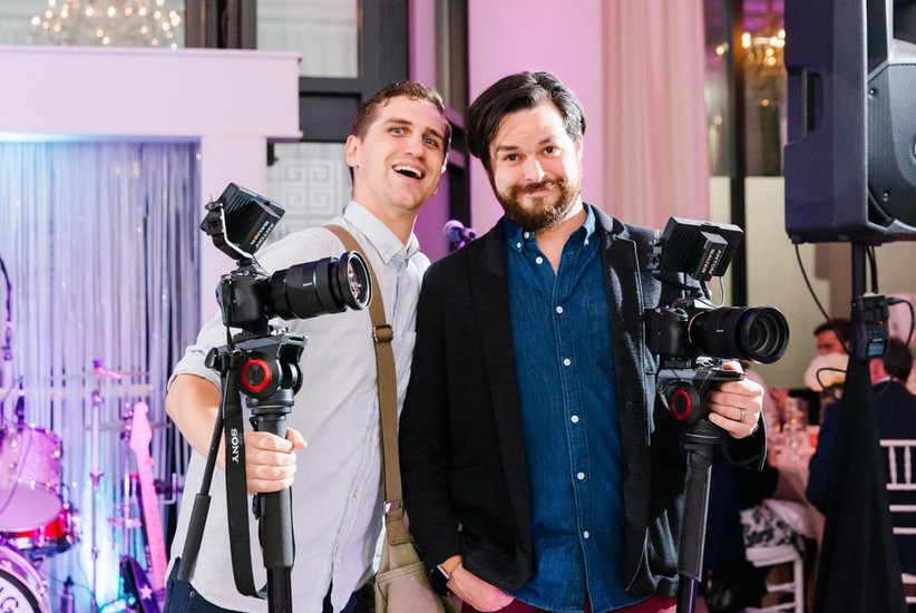 team of two male videographers pose for a photo at wedding reception with their equipment