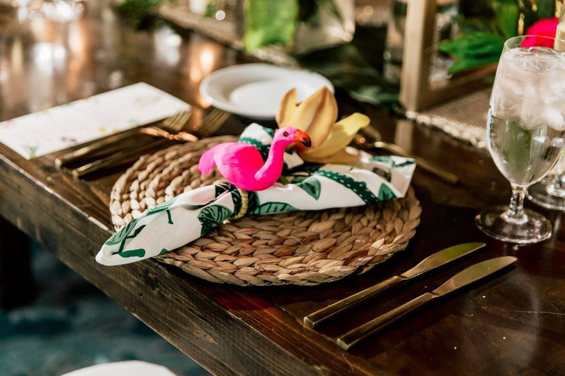 beach wedding place setting with woven rattan charger and flamingo napkin ring with greenery print napkin