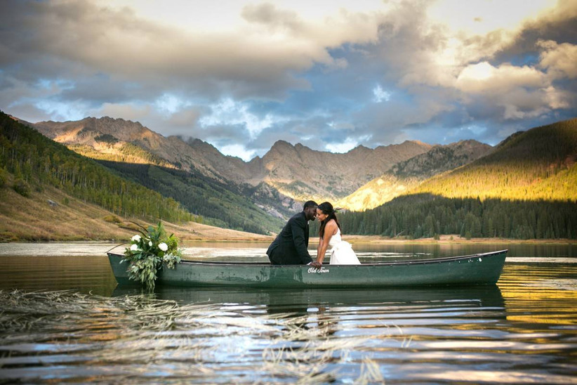 wedding couple sitting in a green canoe with mountains in the background