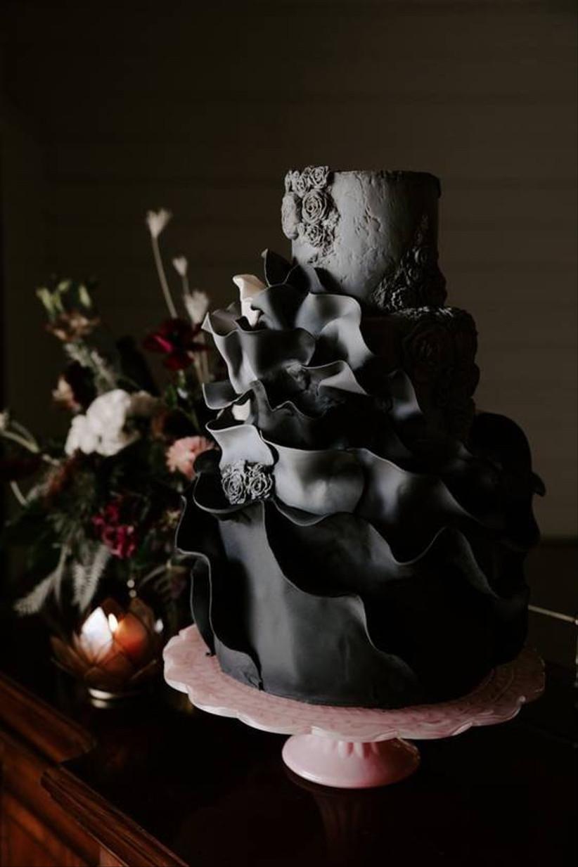 black wedding cake with ruffled fondant