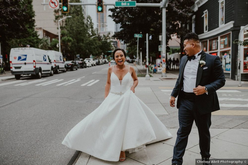 bride and groom walking down city street and laughing