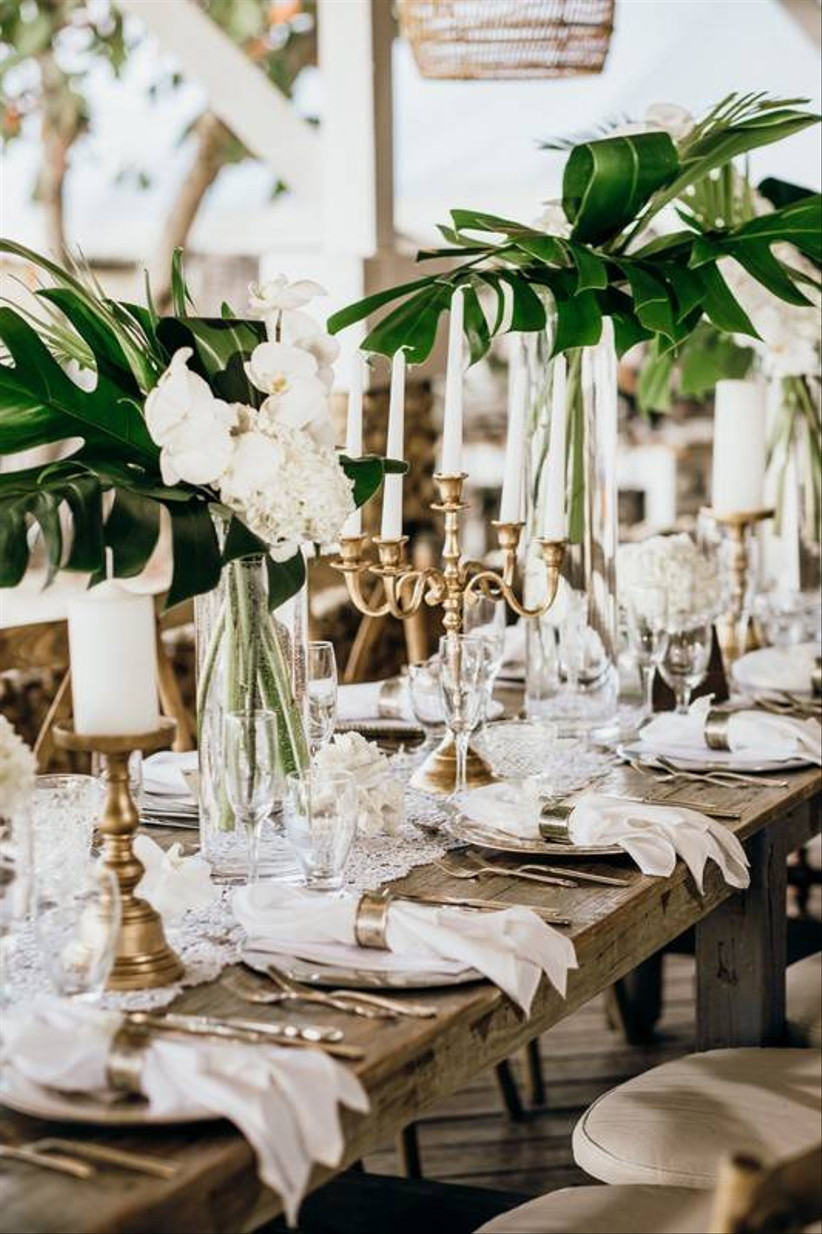 modern beach wedding centerpiece with white phalaenopsis orchids and monstera leaves in tall vases accented with gold candelabras and white taper candles