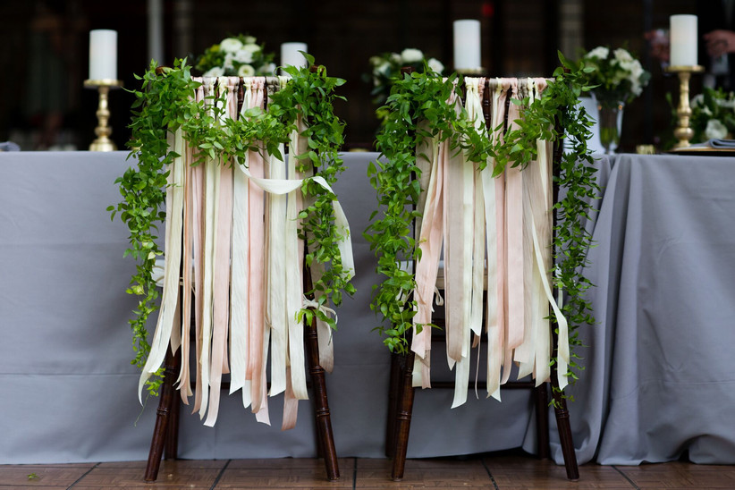 wedding chairs decorated with long pink ribbons hanging down the back and greenery garlands