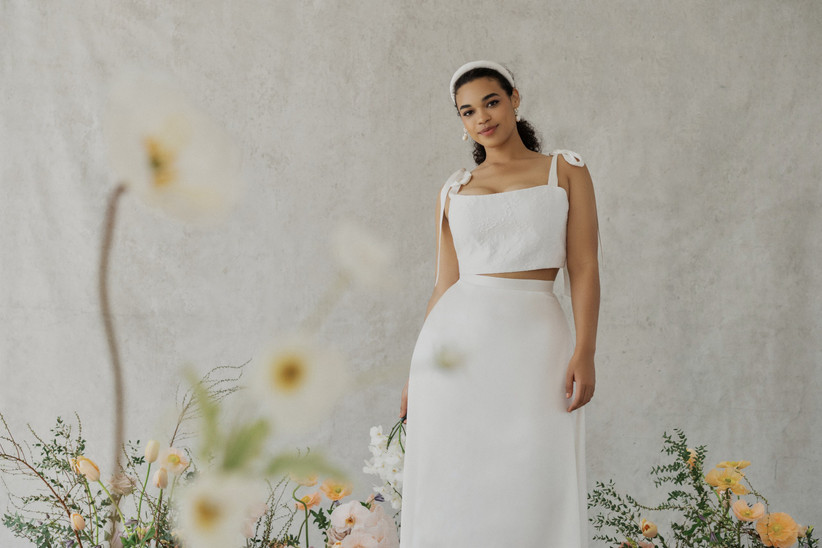 model wears two-piece bridal ensemble white crop top with midi skirt and stands against a white backdrop surrounded by flowers