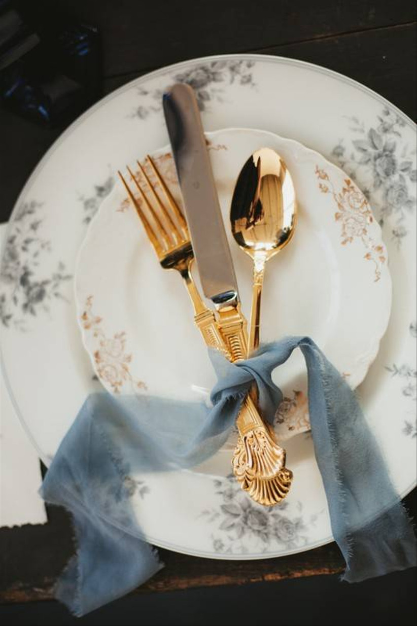 close up of gold knife, fork, and spoon tied with a light blue ribbon