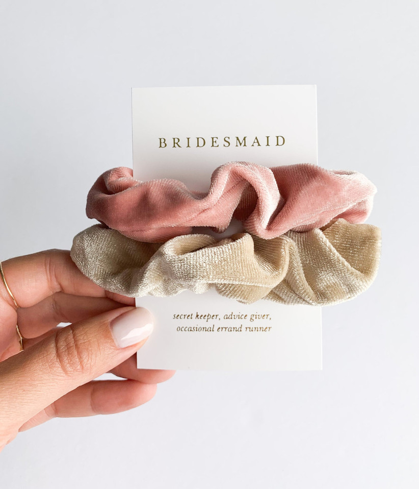 Close-up of a woman's hand holding up a pack of two scrunchies with a definition of a bridesmaid on the packaging