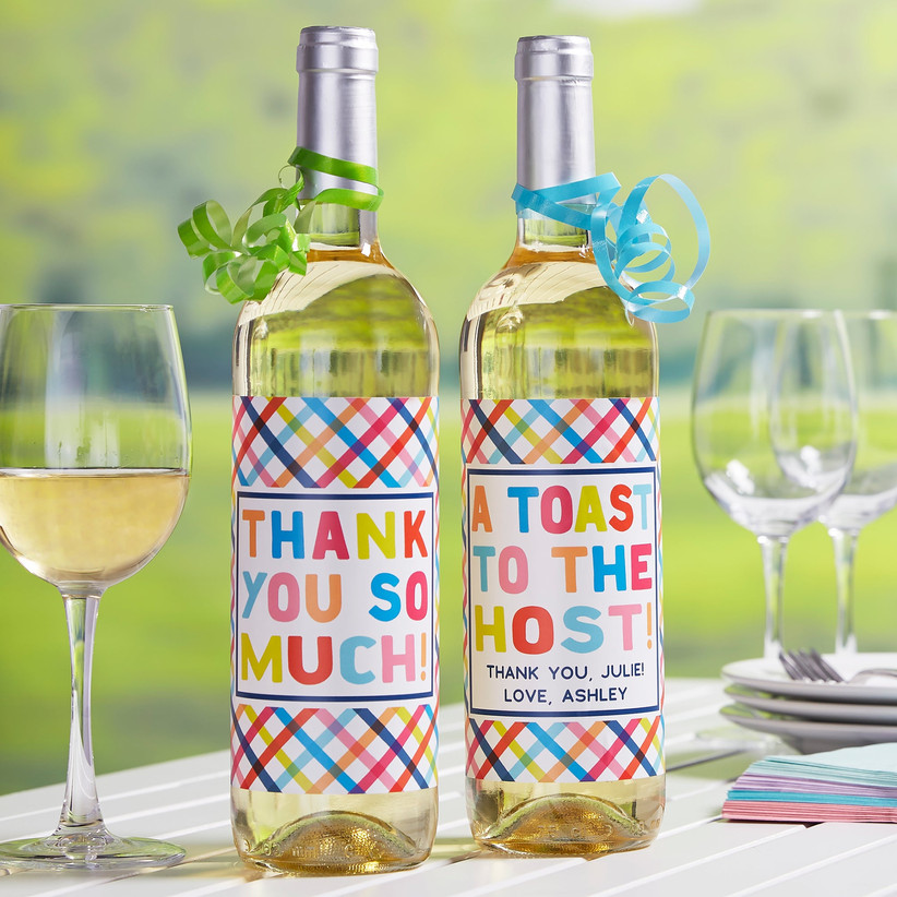 Two bottles of white wine with colorful personalized labels that read Thank You So Much and A Toast to the Host