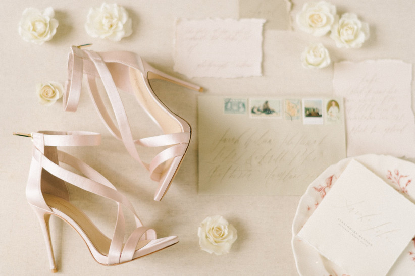 wedding shoes, invitations and fresh flowers are displayed together