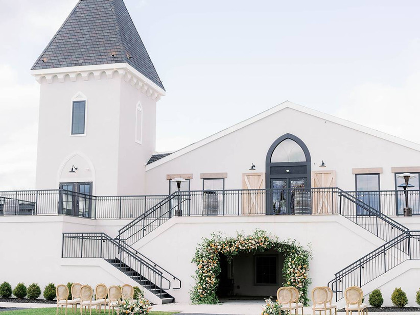 modern barn-style reception venue with grand double staircase on exterior of building