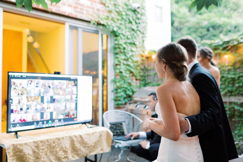 bride and groom looking at a large screen which shows guests via zoom