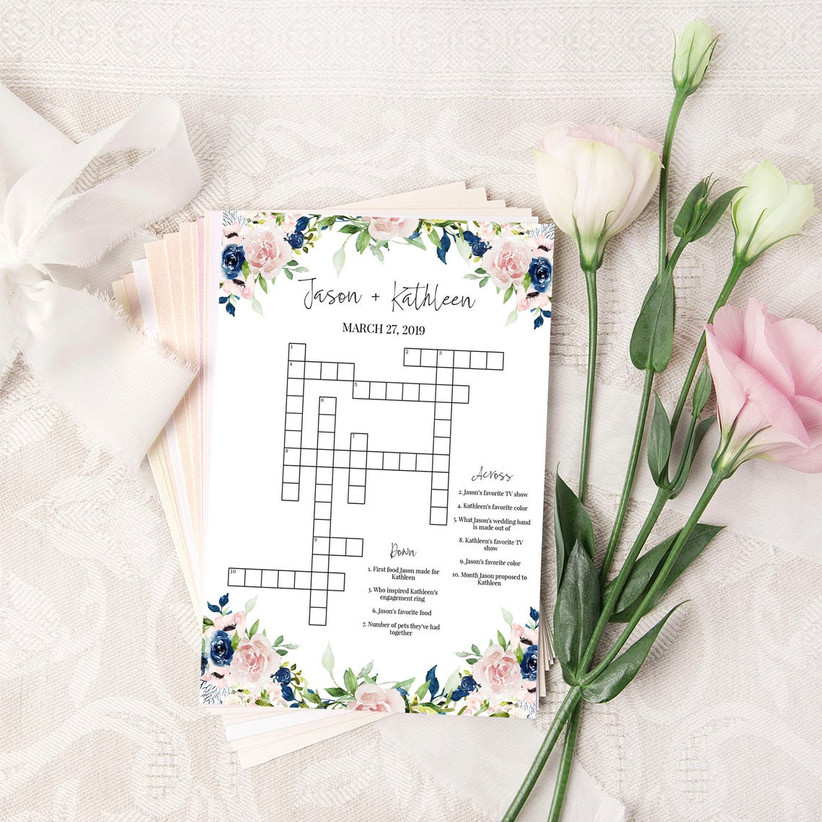custom wedding crossword puzzle with pink and blue flower border and couple's names with wedding date