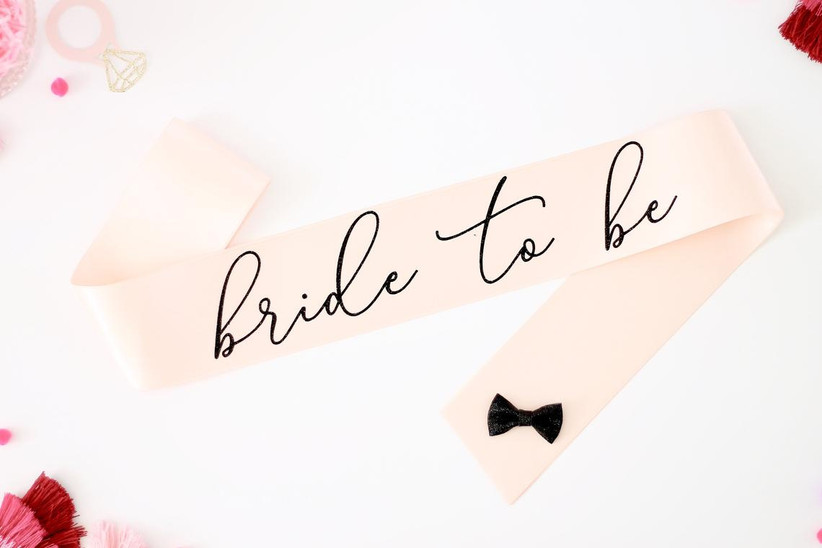blush bachelorette party sash with black bow and