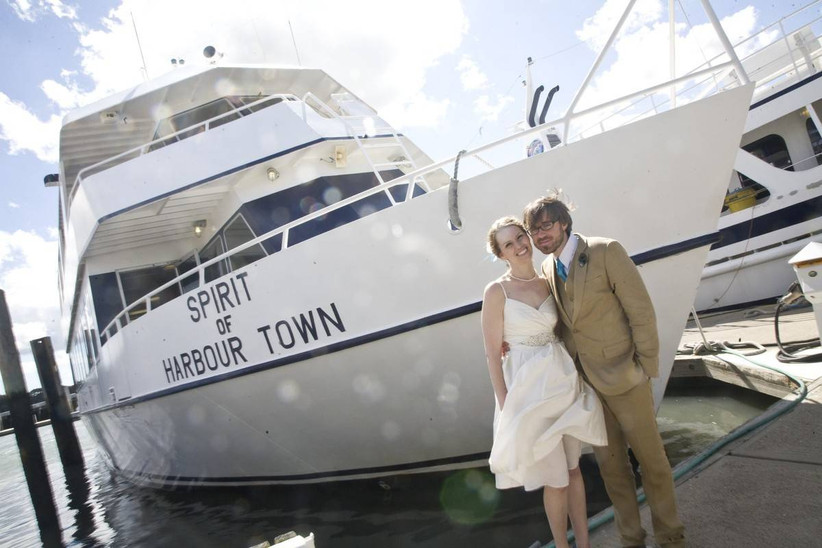 couple posing in front of boat
