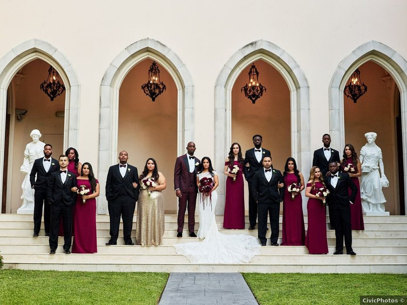 bride and groom, a black couple, stand on the steps of a museum with their wedding party who are wearing tuxedos and long burgundy gowns