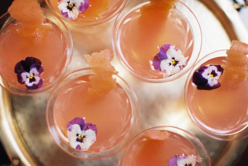 coupe glasses filled with sparkling rosé and topped with edible purple pansy flowers