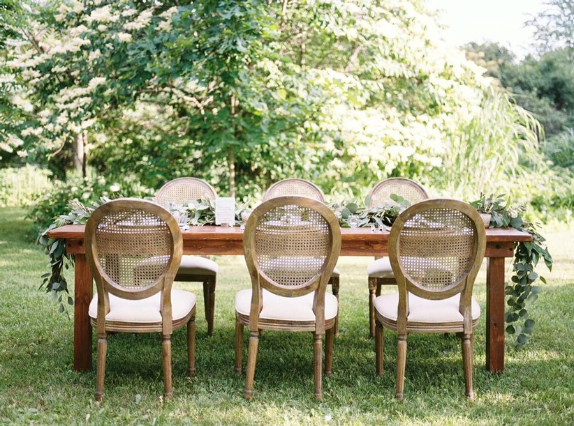 reception table set up outside in the grass with six cane back chairs and greenery for the centerpiece