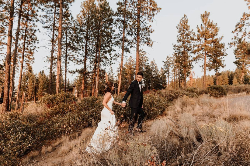 bride and groom walk up a hill while holding hands