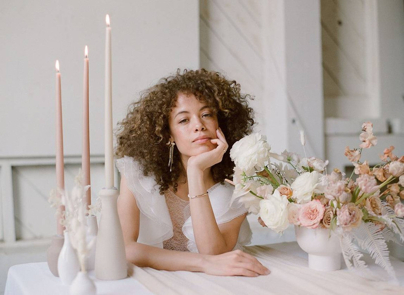 Bride sits at a table and looks into the camera with her chin in her hand and blush wedding centerpiece on one side with long taper candles on the other side