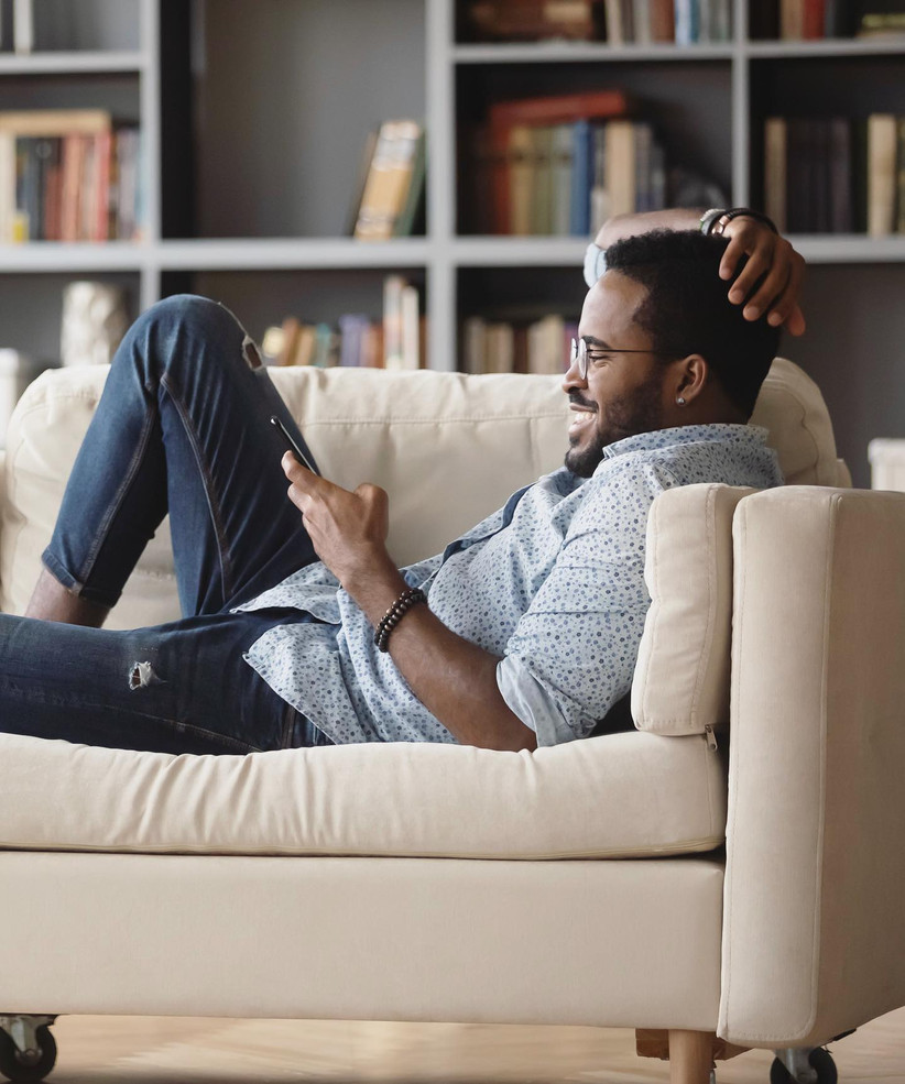 Man lounging on sofa smiling at his phone wearing blue light glasses