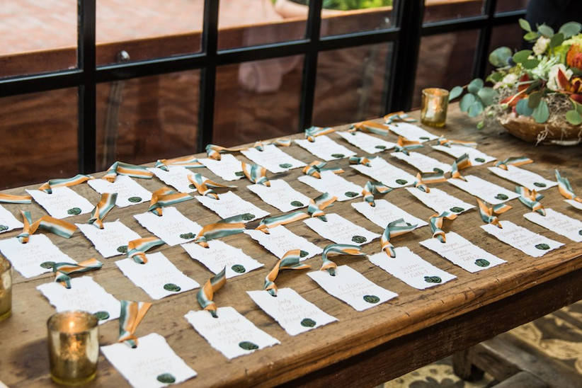 raw-edge wedding escort cards decorated with gold wax seals and colorful ribbons