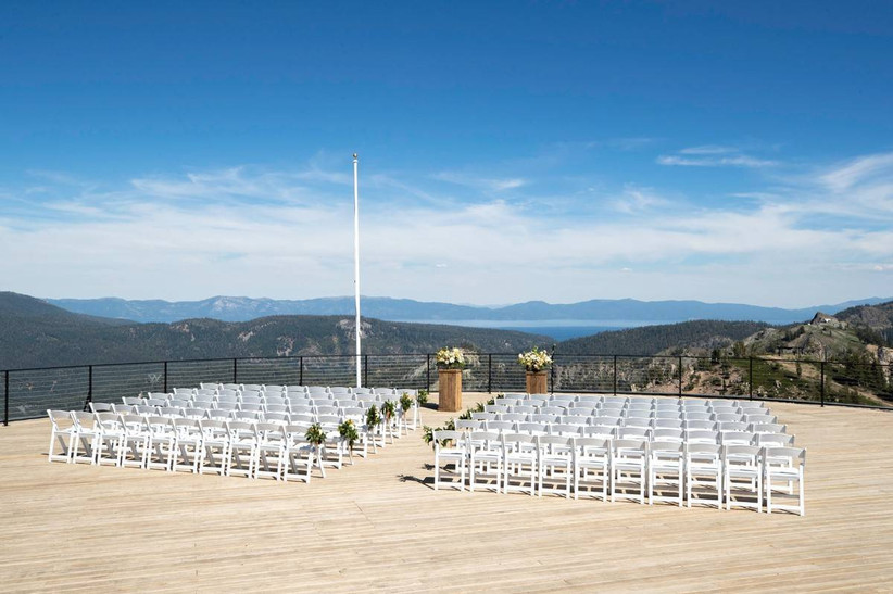 aerial view of mountaintop wedding venue at lookout deck on a sunny day. rows of folding white chairs are lined up facing the view