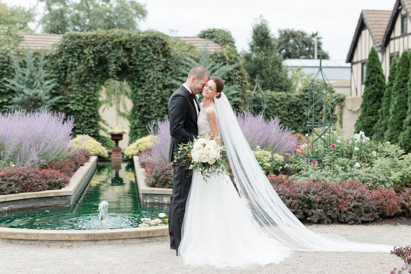 bride and groom pose in front of stone fountain surrounded by lavender and other flowers at botanical gardens wedding venue