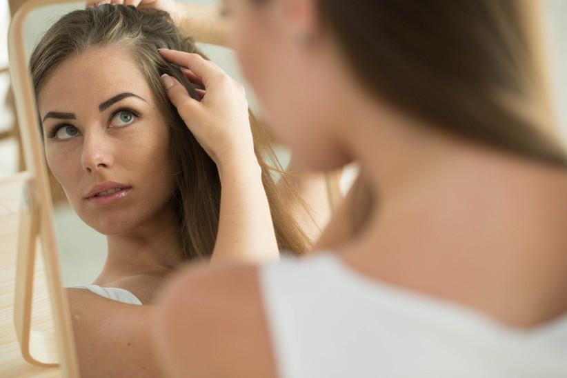 woman checking hair in mirror