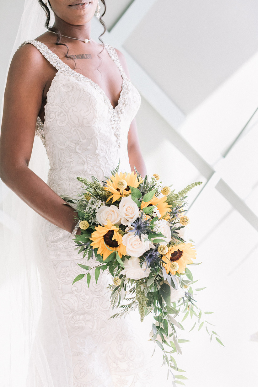 Black bride holds cascading sunflower wedding bouquet with white roses and greenery