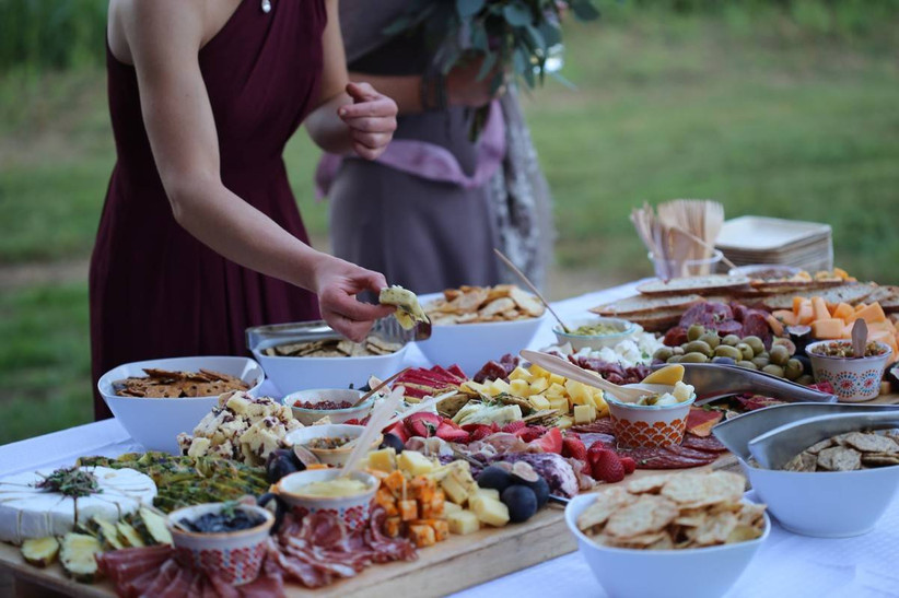 woman taking food from charcuterie board