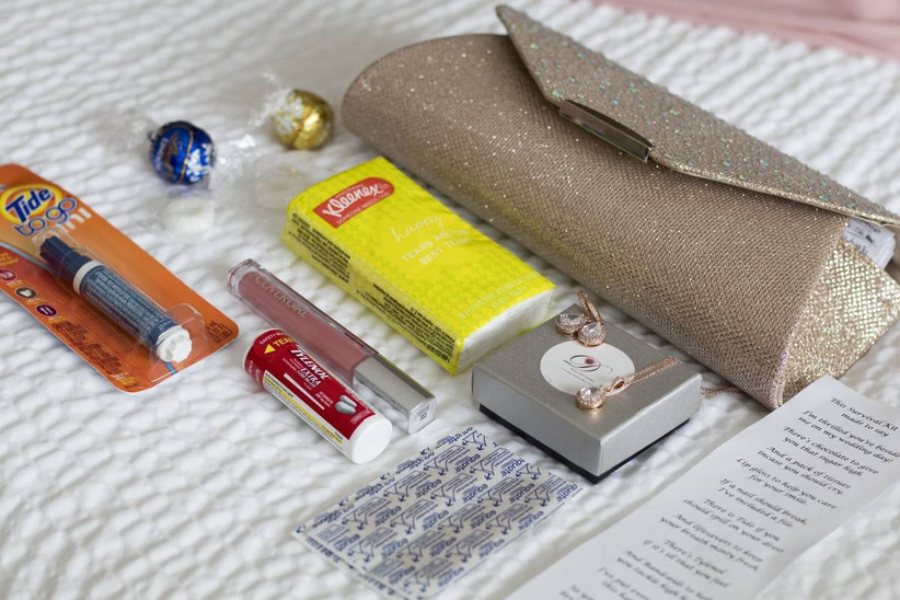 gold clutch with various items laid on a bed tissues, tide pen, tylenol, chocolates